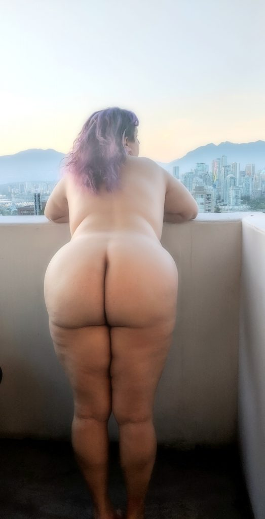 A naked woman gazing over the city and the mountains, in soft focus mode, with. Butt exposed.